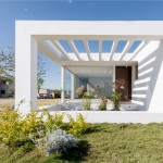 Glass walls and terraces frame views from bright white house in Argentina