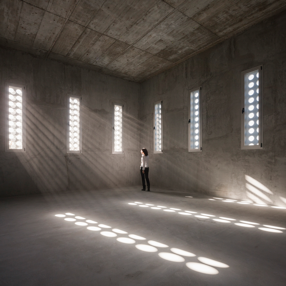 Circular perforations create natural spotlights inside Elisa Valero's concrete school extension