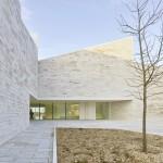 Pale travertine walls frame Cour et Jardin cultural centre by Atelier Fernandez & Serres