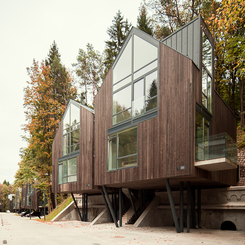 Timber-clad houses raised up on stilts over ammunition vaults in Vilnius parkland