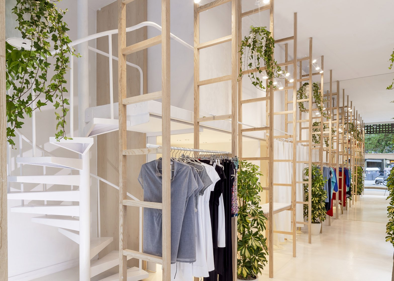 Clothes hang from wooden ladders in Mit Mat Mama store