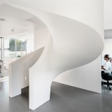 Villa Lumi by Avanto Architects has a curving white concrete staircase