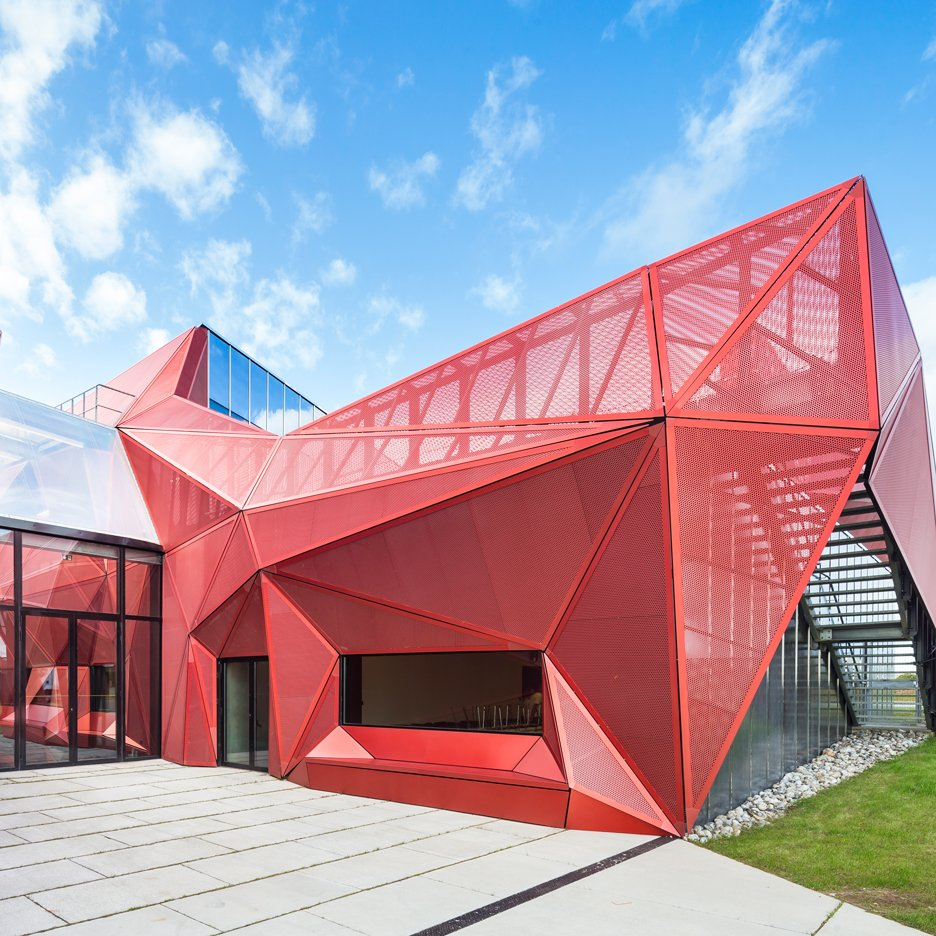 Faceted Red Metal Creates Sculptural Facade For Music