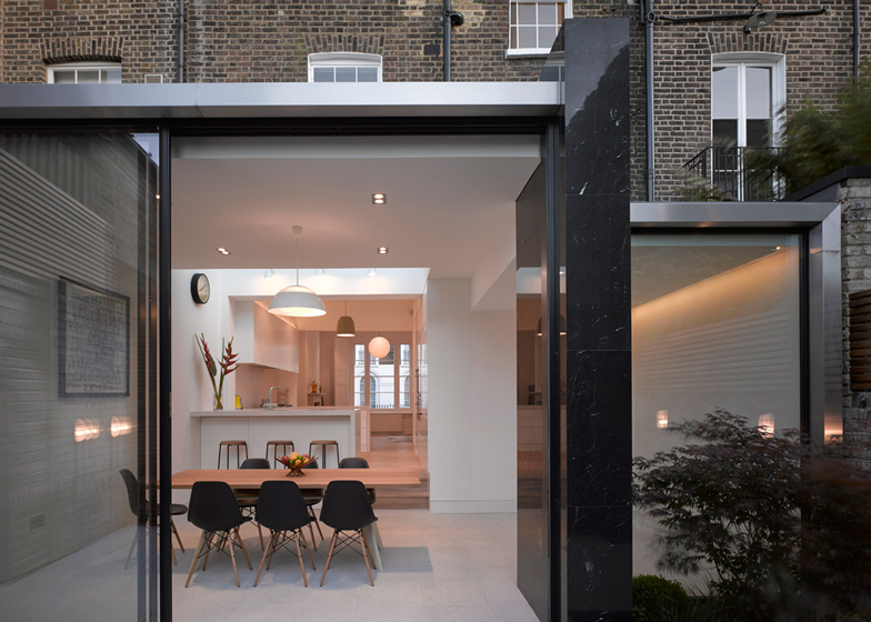 A glossy black marble wall divides this extension to a 19th-century townhouse by Paul Archer Design
