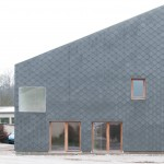 Cement shingles create scaly facade for French barn conversion by GENS