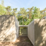 Sculp IT organises concrete boxes around glass corridor to create Belgian woodland home