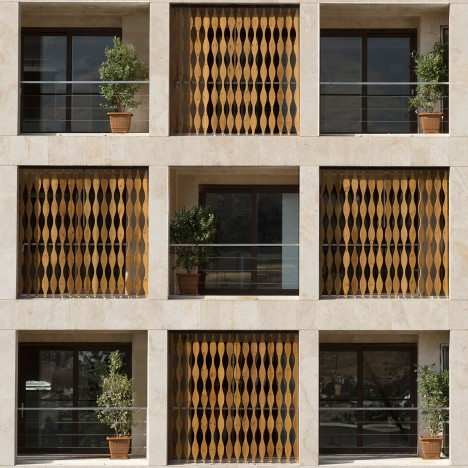Wavy wooden shutters cover gridded apartment block in Iran by TDC Office