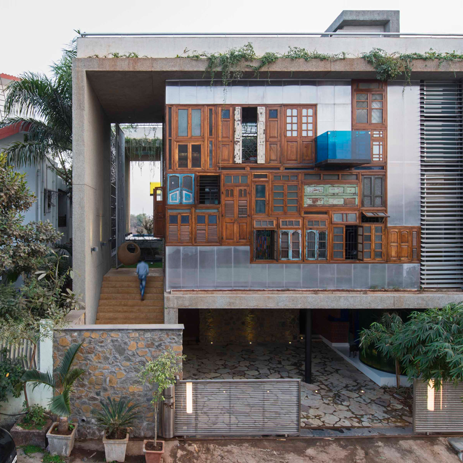 Reclaimed windows and doors form facades of collage house for Window design for house in india