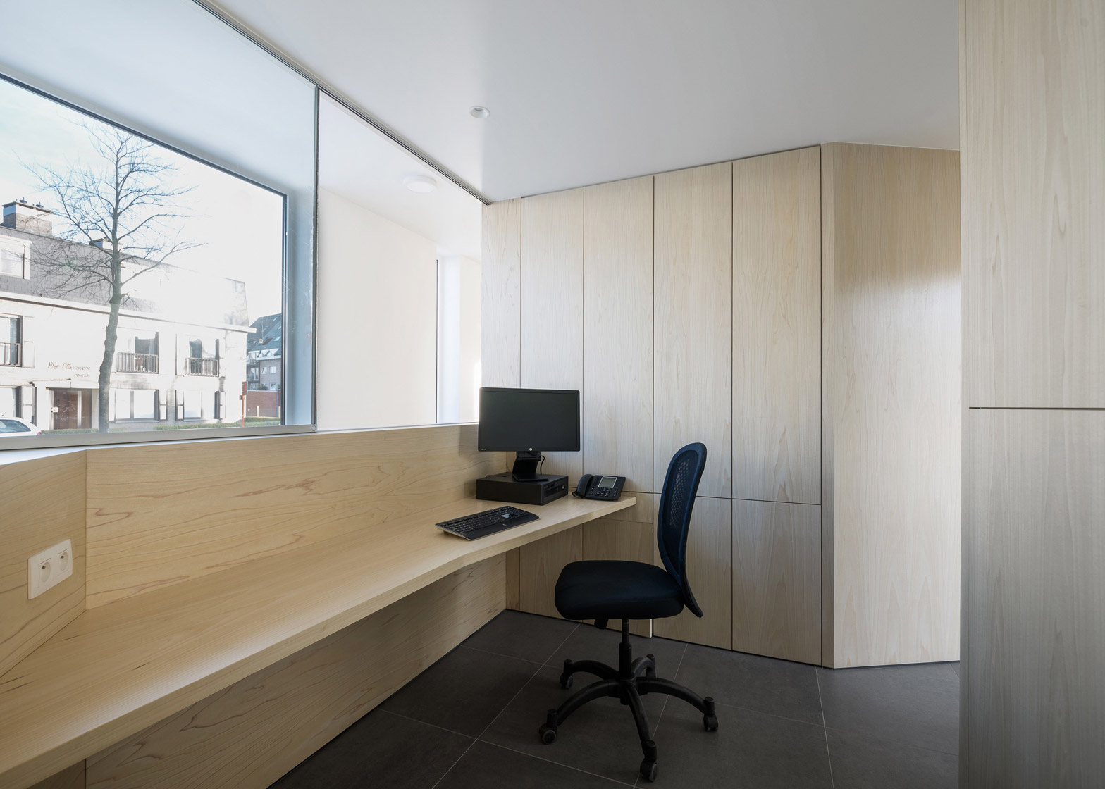 Joshua Florquin uses angular joinery to create bespoke furnishings for doctor's surgery in Maldegem, Belgium