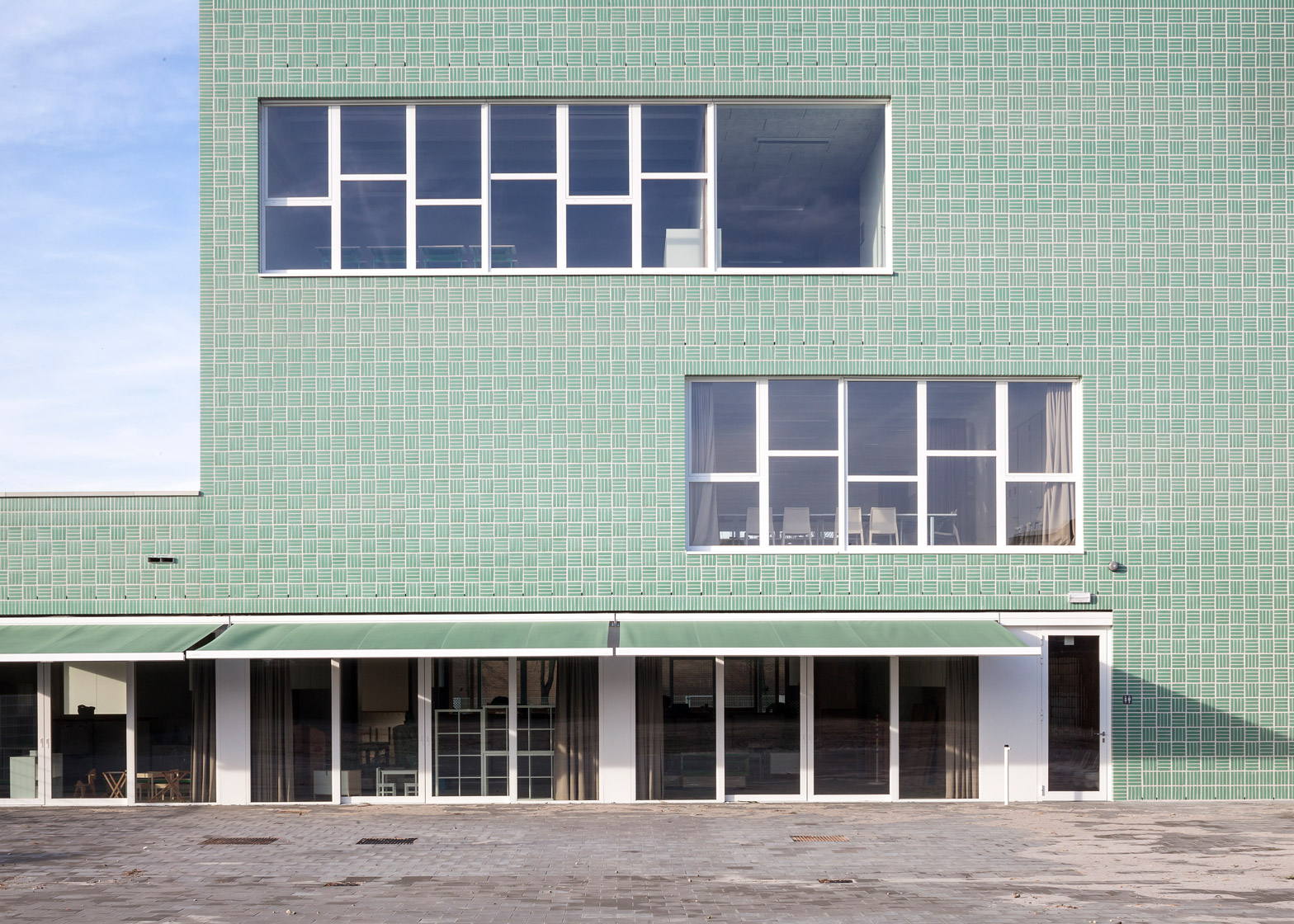 green bricks lend woven texture to school by areal architecten