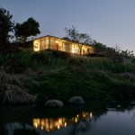 Riverside house by Architecture Brio is partially embedded in a grassy hillock