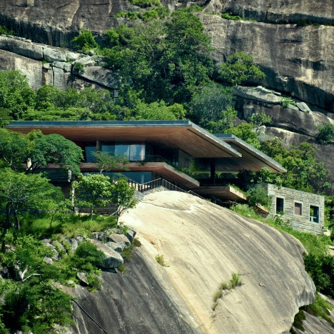 Timber and granite residence by Studio Seilern stands on a rocky ledge above an African dam