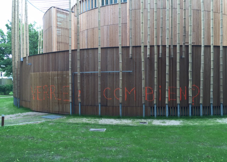 "Orange graffiti on the theatre's wooden exterior read ""Wart? What cost?"""