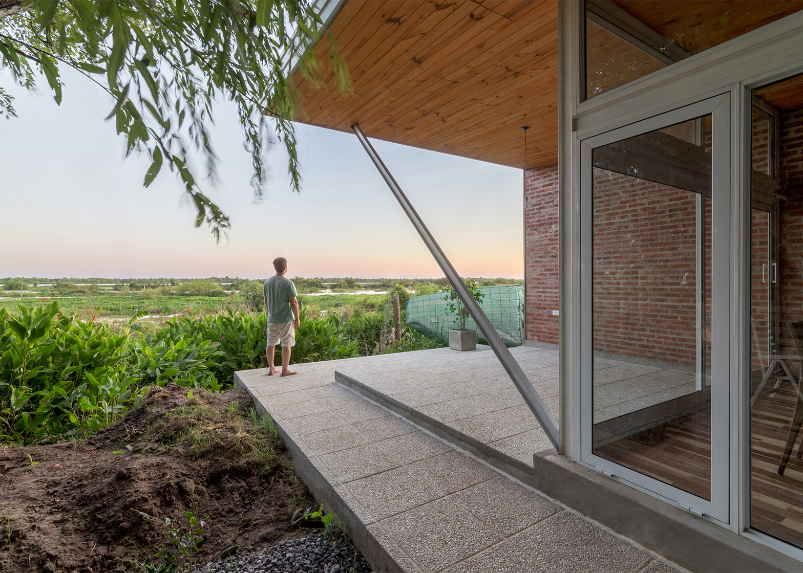 House 50 50 by Celula Urbana sits next to a river in Argentina