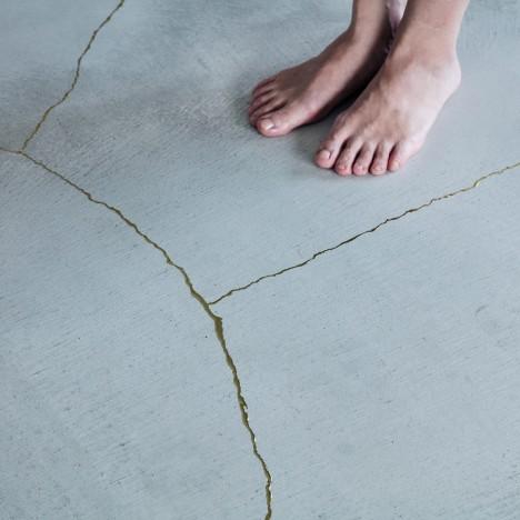 Golden resin highlights cracks in the floor of TANK's Xchange Apartment