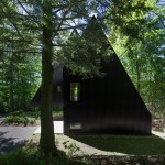 Jean Verville creates black fairytale-like cottage in a Quebec forest