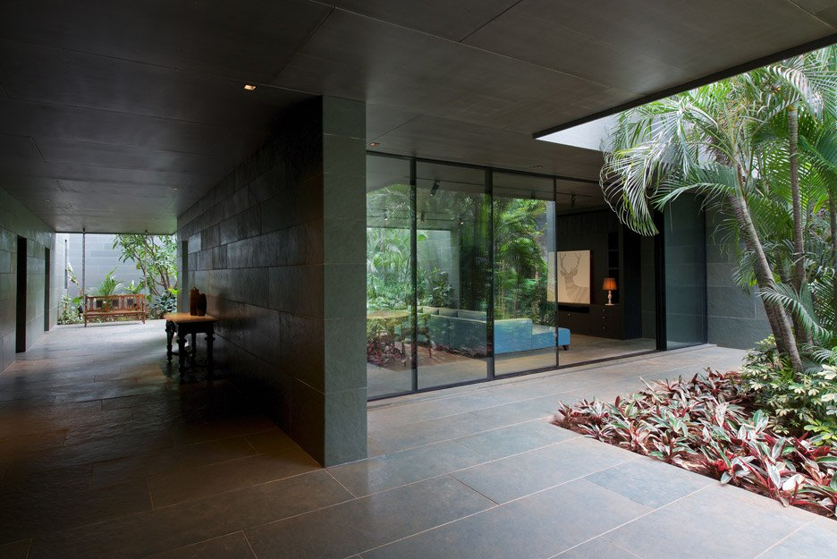 Spasm Architects clad Indian house in local stone and wrap it around a sunken courtyard.