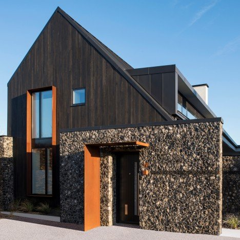 Rugged flint walls contrast dark cedar gables of House 19 by Jestico and Whiles