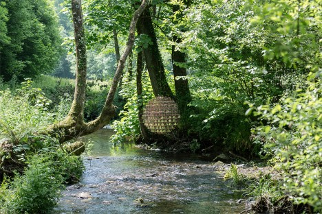 "Giles Miller's Penny-Half Sphere sculpture is a ""double-sided portal"" hanging above a stream"