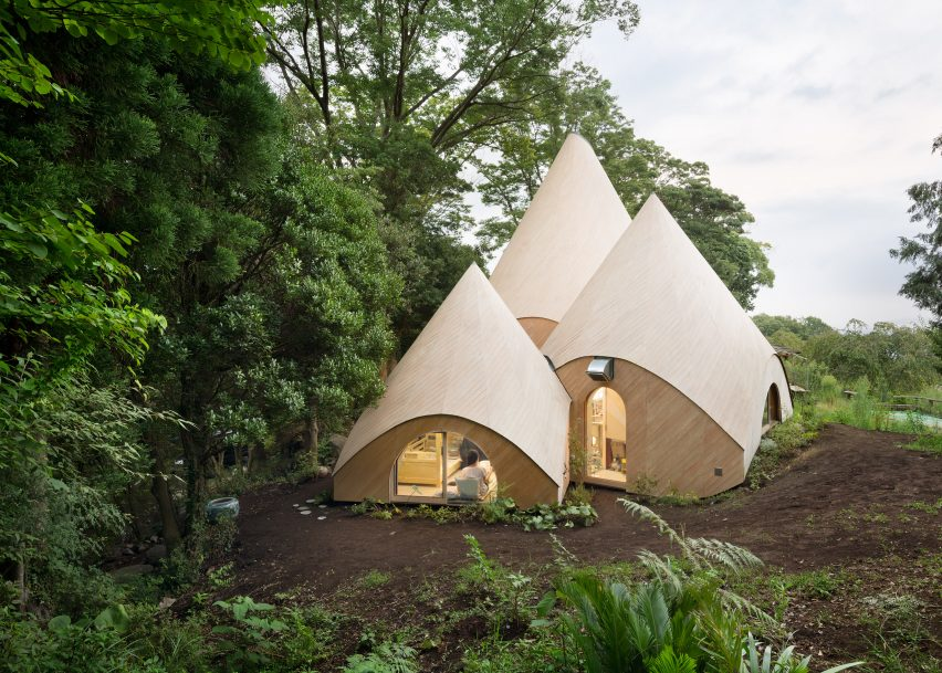 Teepee-shaped buildings by Issei Suma house community kitchen and spiral-shaped pool