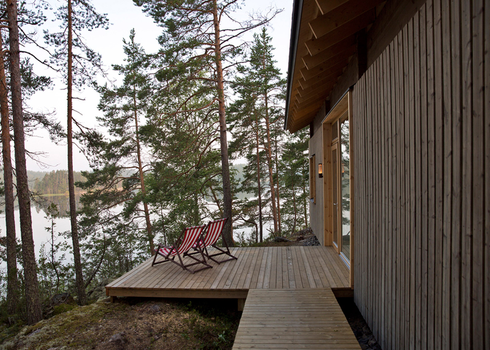 Lake cabin by Sini Kamppari features slatted timber siding and projecting terrace