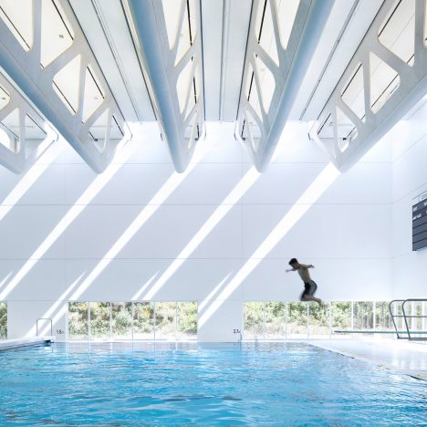 "Beams of daylight ""streak across the walls"" at Bing Thom's aquatics centre in British Columbia"