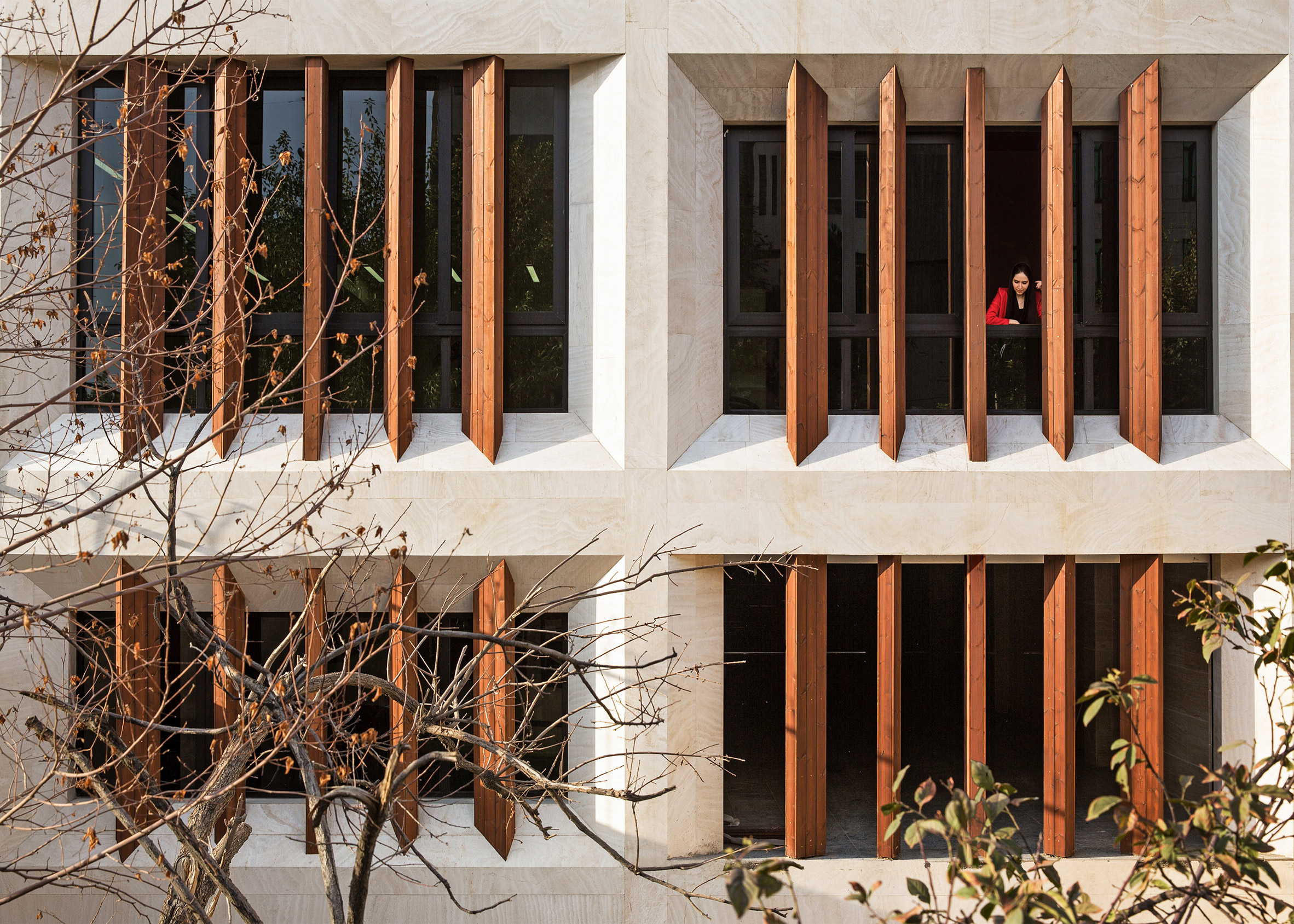 Tehran office building features facade divided into a grid of faceted window frames