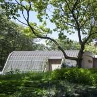 Ambulance station by Architectenforum features plant-covered walls and a curved roof