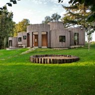 Overlapping cylindrical and log-covered blocks form Danish holiday home by Jan Henrik Jansen