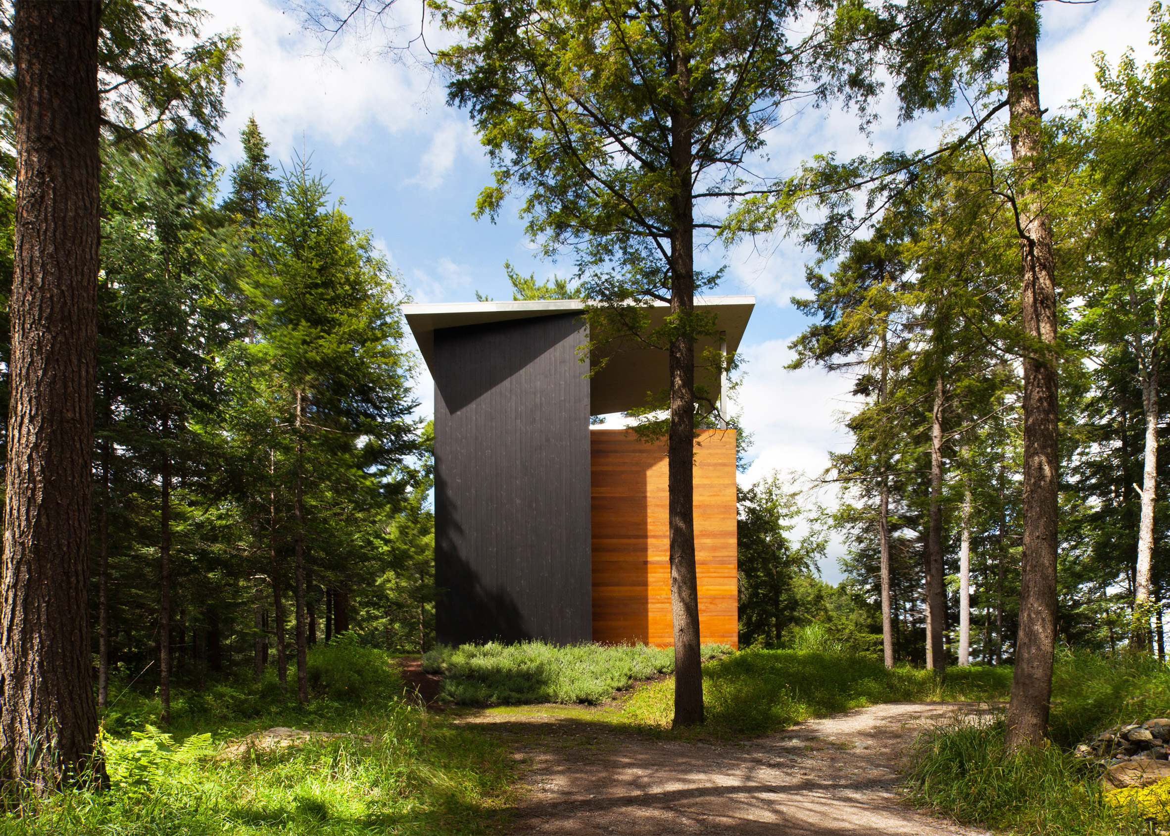 YH2 clads a Quebec holiday home for a sculptor in red cedar and blackened pine