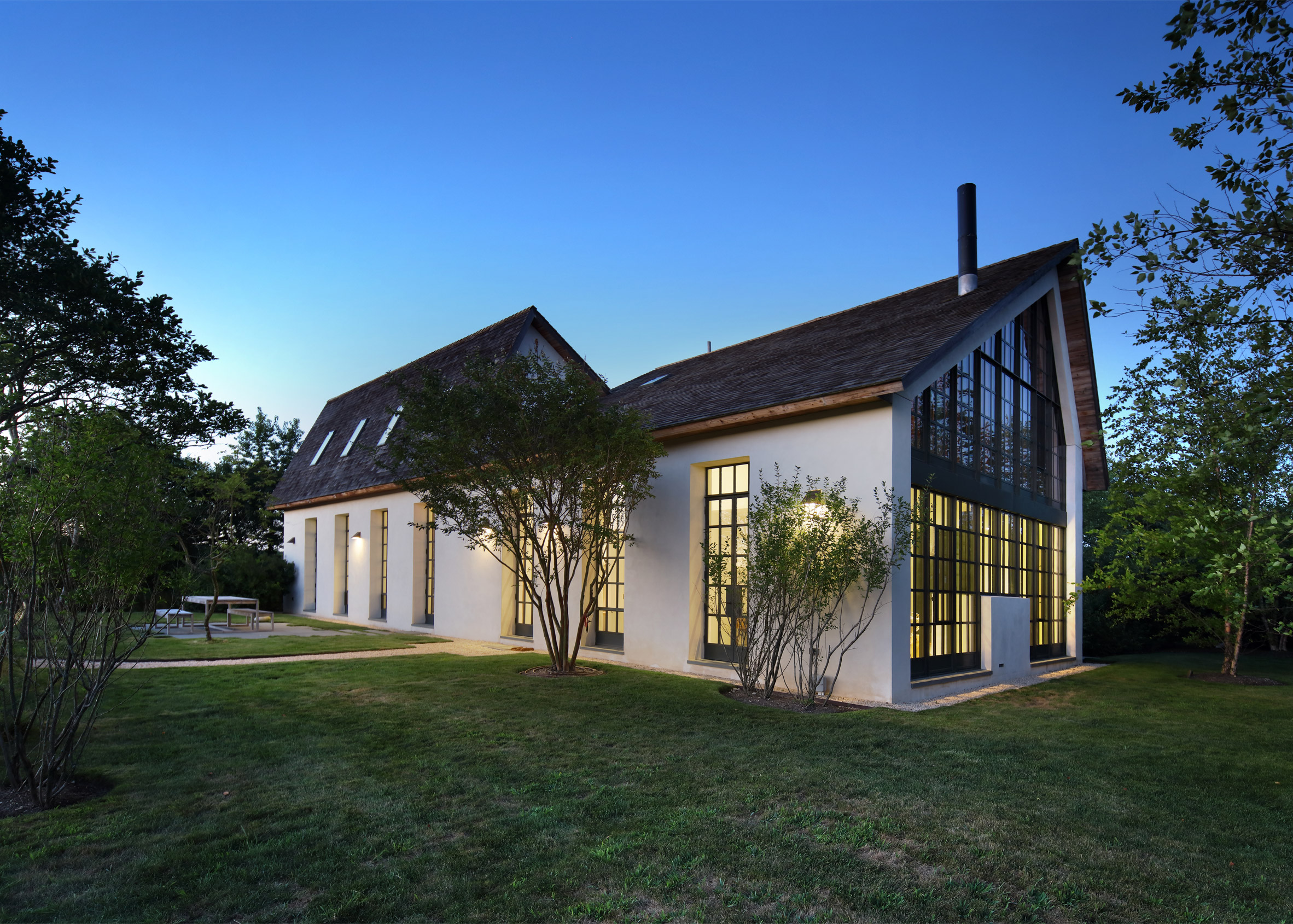 TA Dumbleton creates a Hamptons guest house with stucco walls and steel casement windows