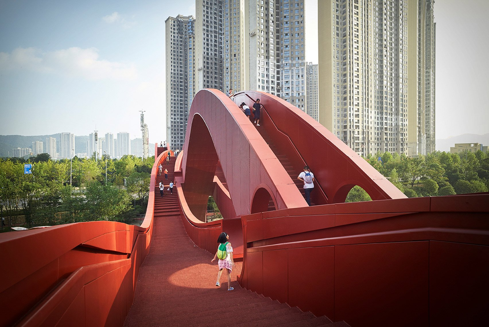 Wavy red ribbons form Lucky Knot bridge by NEXT Architects