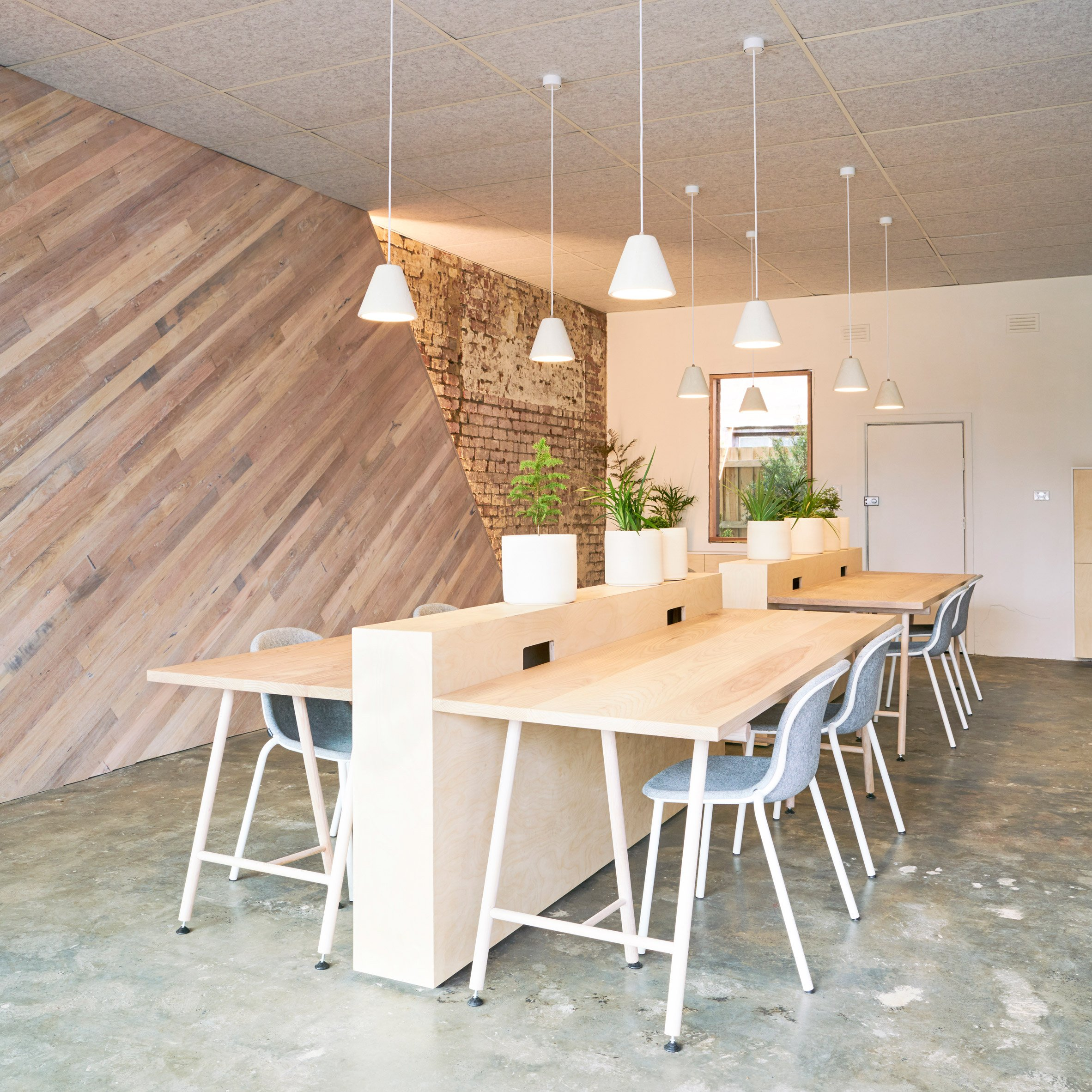 Collective workspace in Melbourne features plank-covered walls and bespoke furniture