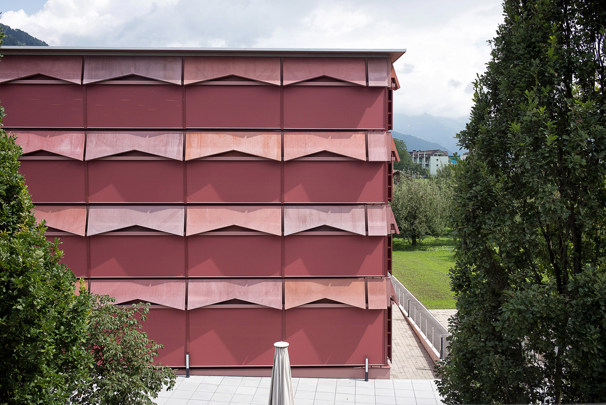 Disability support centre by Architekten CM features tinted concrete ramps and retractable awnings