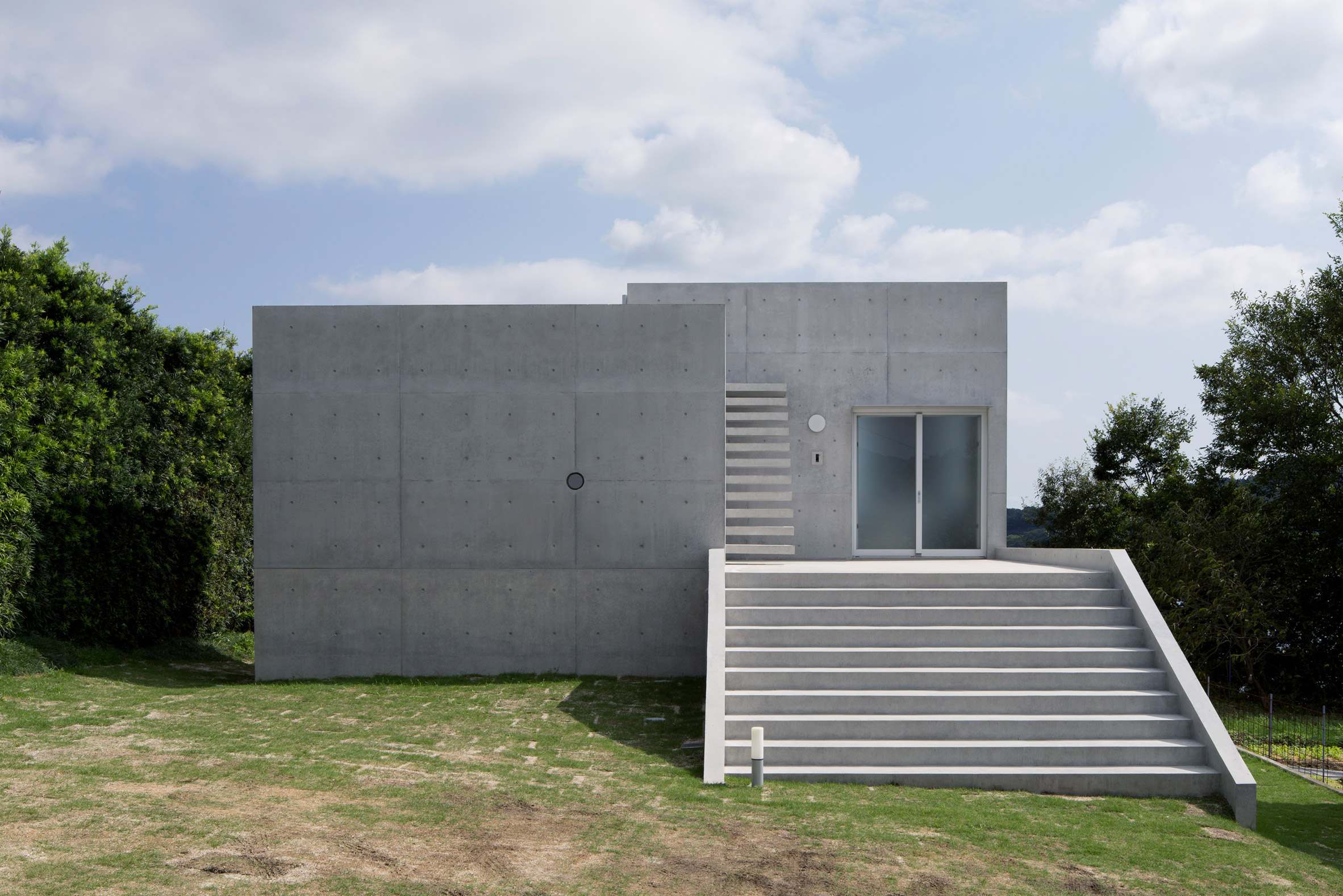 Chunky concrete staircase spirals through House in Akitsu by Kazunori Fujimoto