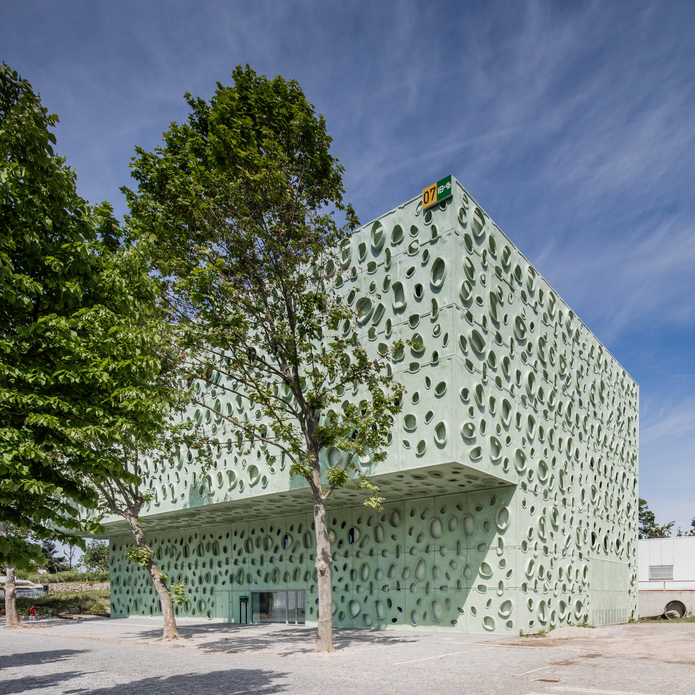 Perforated green cladding wraps university science institute by Cláudio Vilarinho