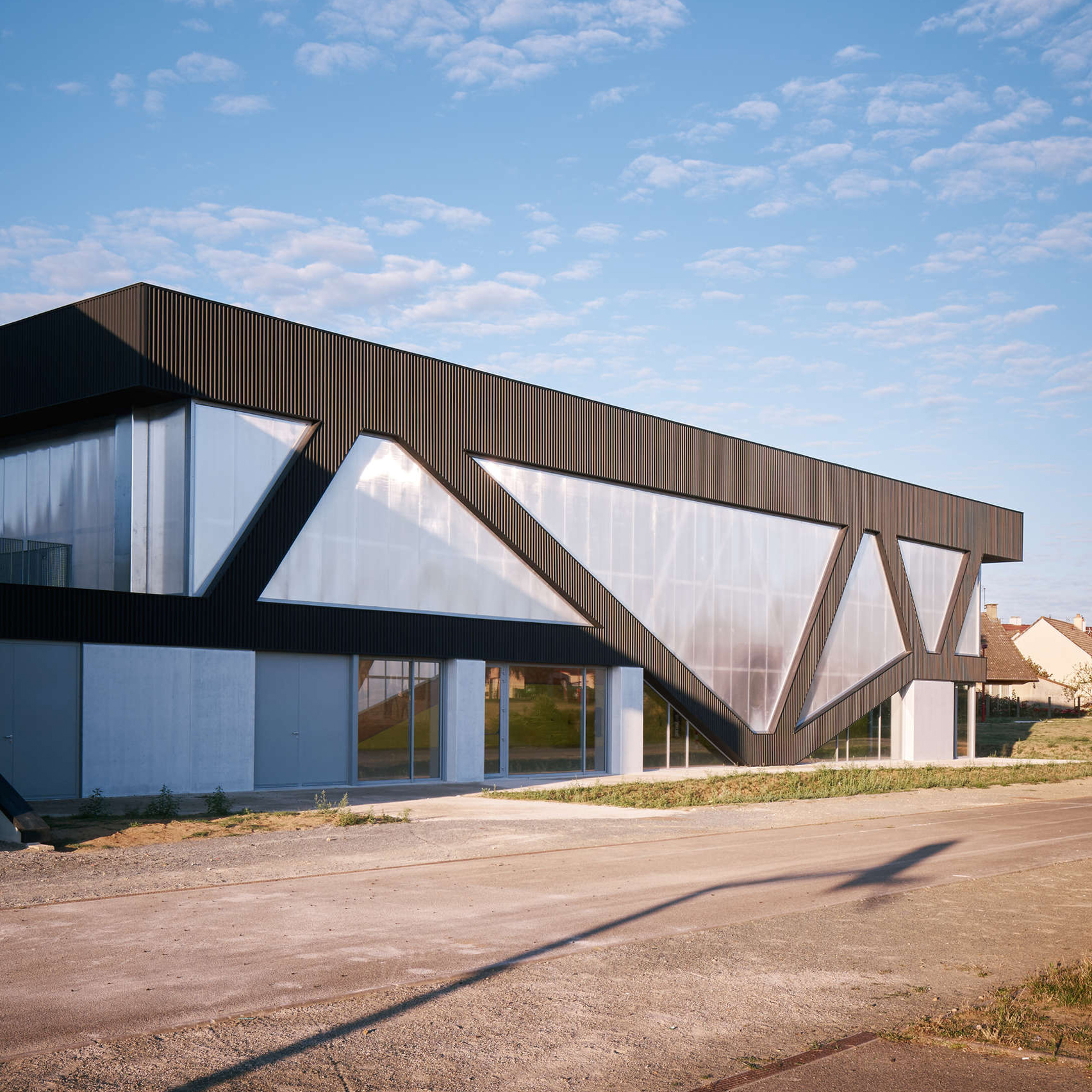 Diagonal beams create irregular windows for sports hall by Schemaa
