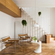 Paris apartment updated with slender white staircase and dark green kitchen