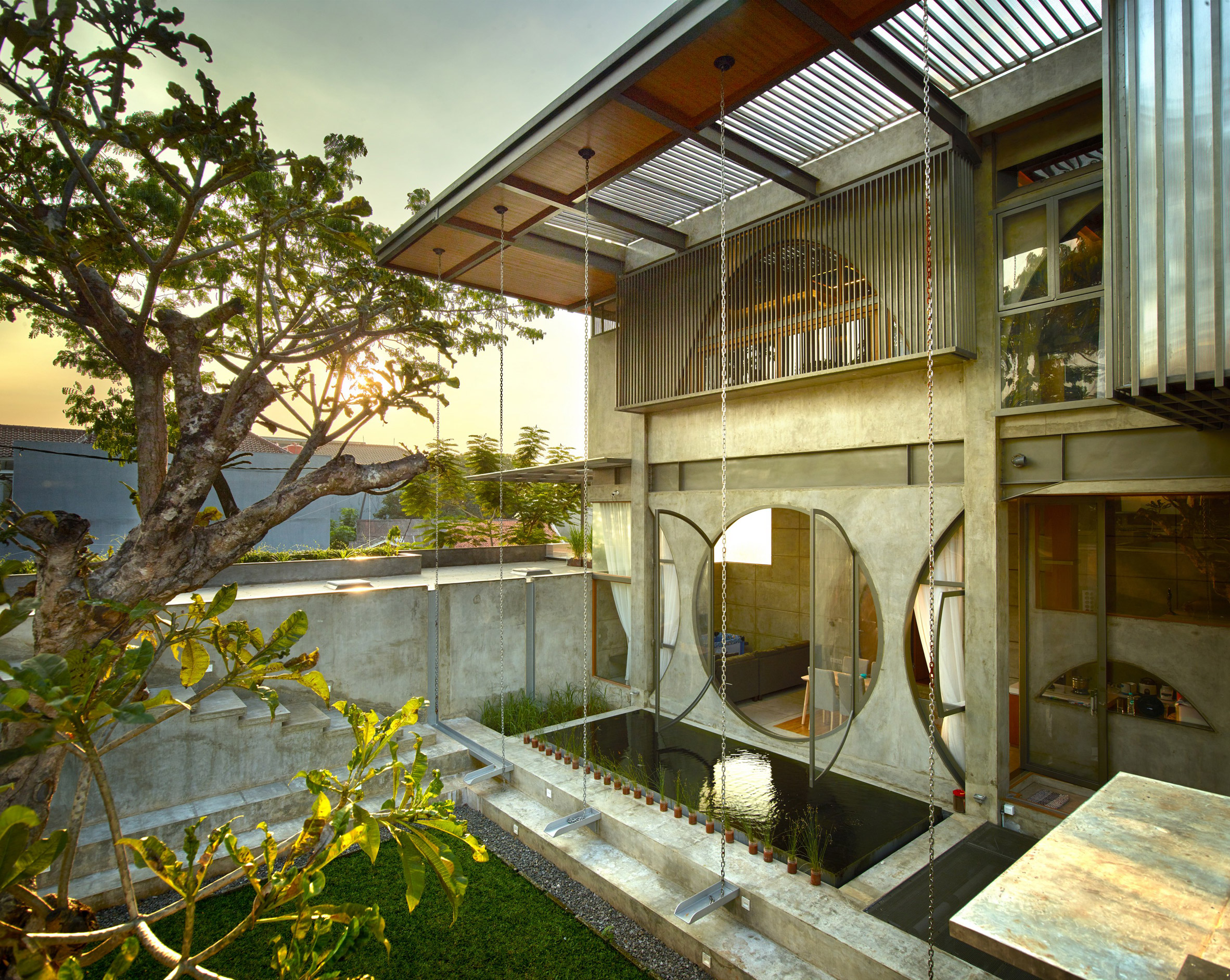 Circular windows and pyramidal skylights add playful geometry to Indonesian home