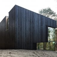 Charred timber and glass villa by VVKH Architecten is embedded in a sand dune
