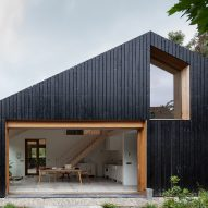 Blackened wood barn by Workshop Architecten houses both livestock and people