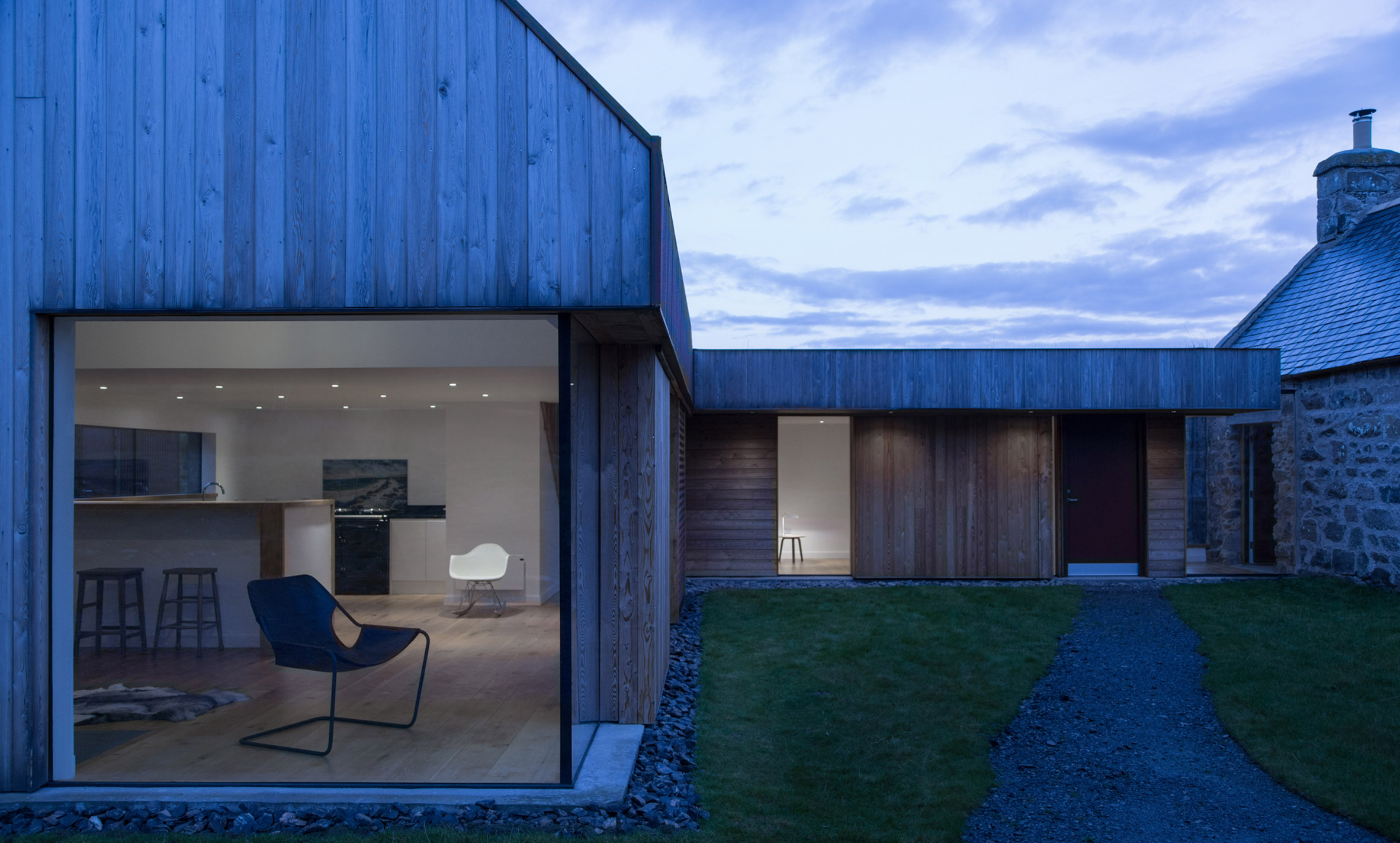 Moxon adds red metal and larch extension to farmhouse in Scottish Highlands