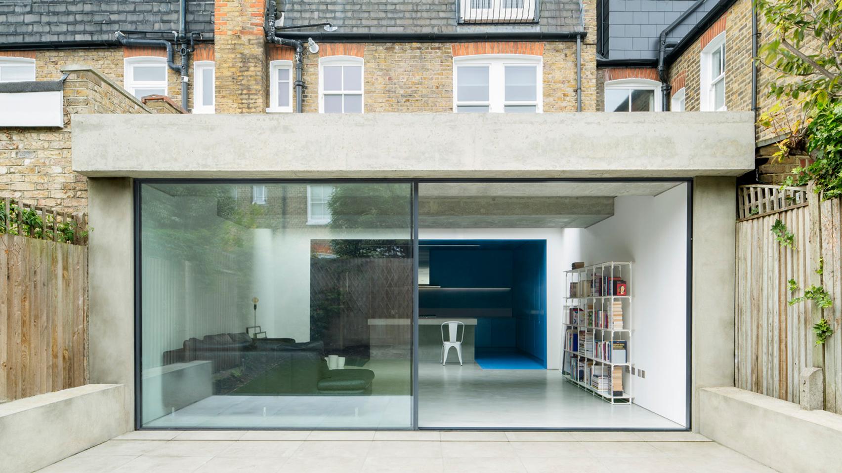 london extension by bureau de change has blue kitchen and white lounge
