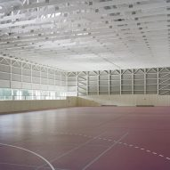Wooden trusses pattern walls of prefabricated sports hall by Florian Fischer and Harald Fuchshuber