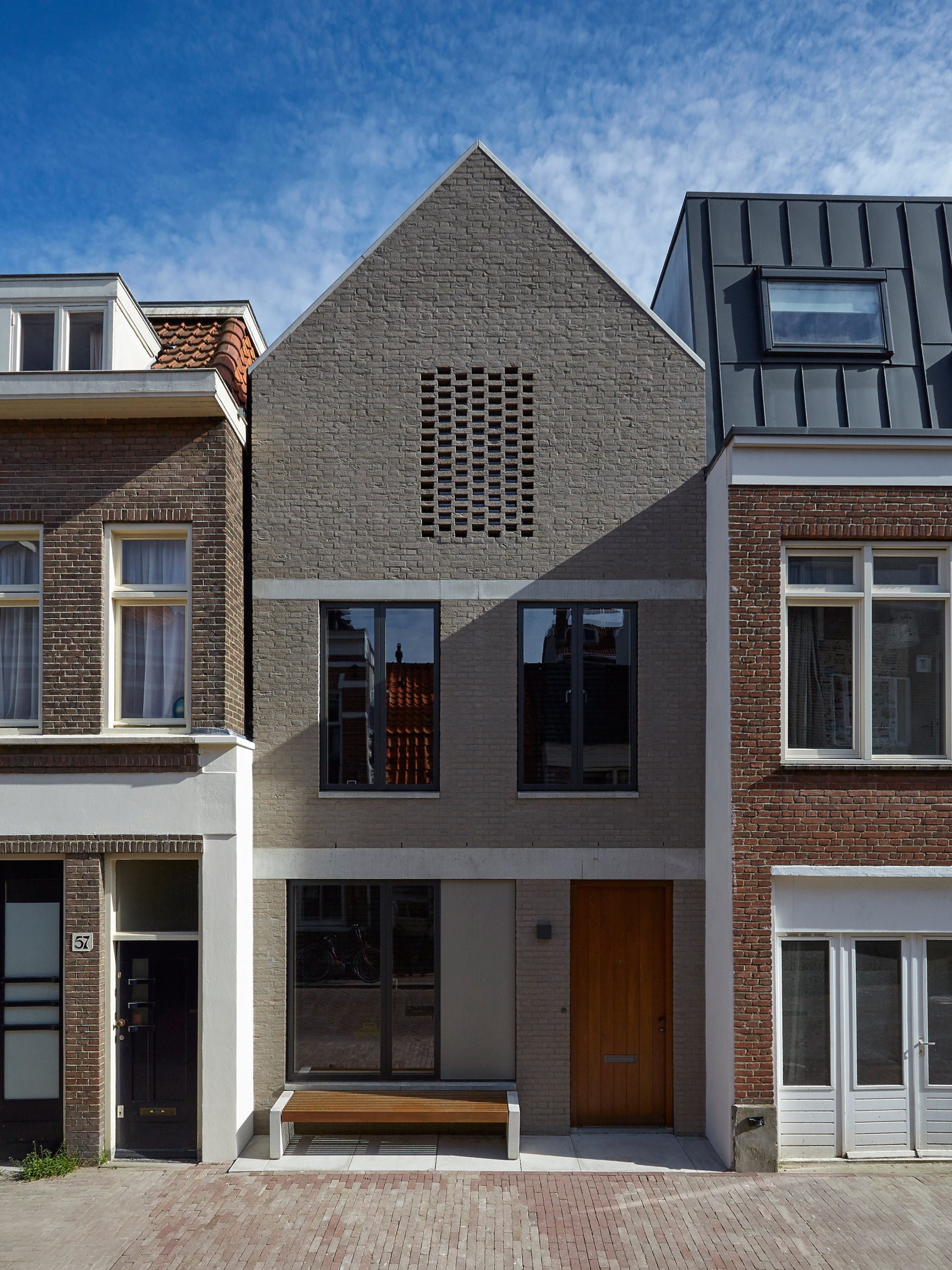 Grey brick Amsterdam townhouse by 31/44 Architects features large rooflight and sunken living room