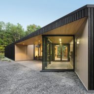 Dark cedar boards shroud Quebec visitors centre by Anne Carrier