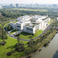 Sandstone-clad blocks encircle central square at island clubhouse in Jiaxing