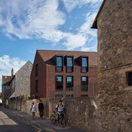 Walters & Cohen covers housing for English boarding house in rusty-red tiles