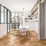 Iron-framed glass panels divide Rome apartment with open-plan feel