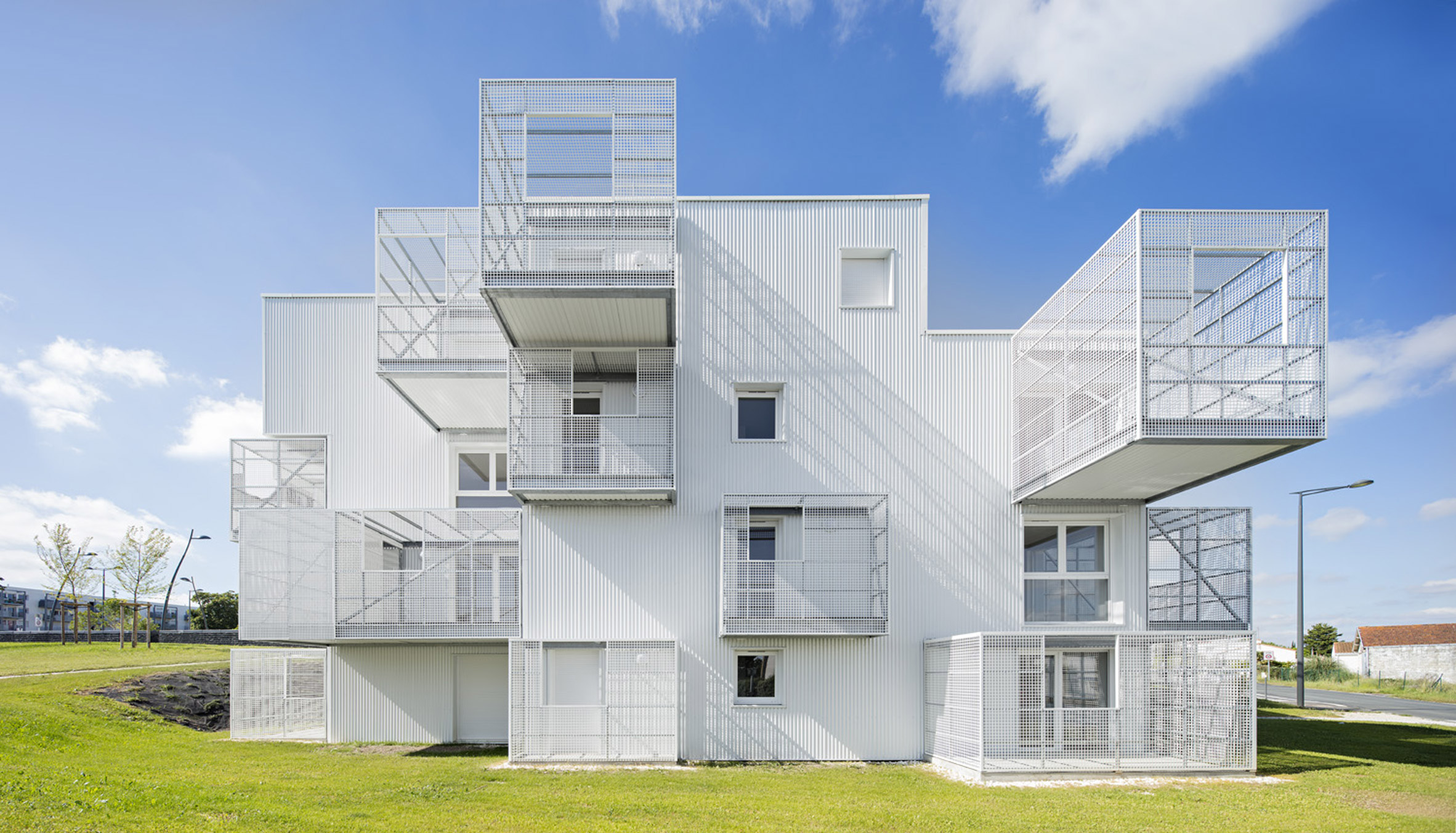 White irregularly stacked boxes form social housing in France by Poggi + More